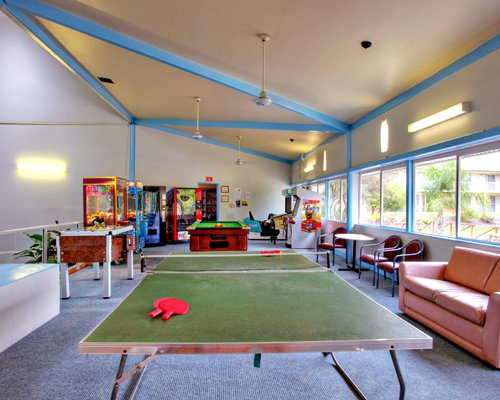 Indoor recreation room with with arcade games pool table and table tennis.