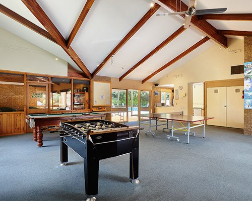 A recreational room with pool table foosball and table tennis.