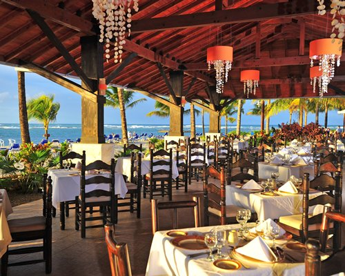 An outdoor restaurant alongside the beach with palm trees.