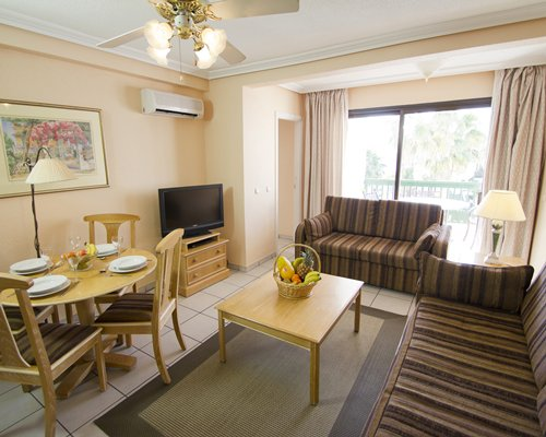 A well furnished living and dining area with television and an outside view.