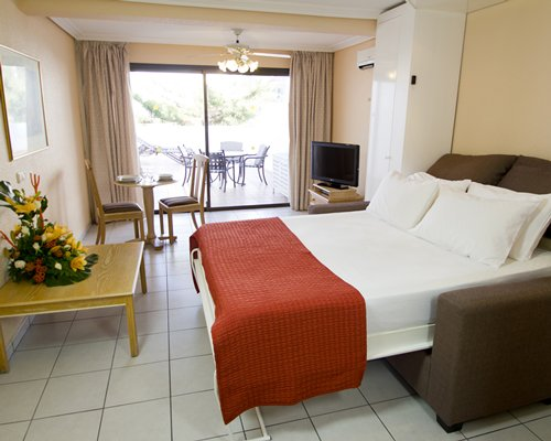 A well furnished bedroom with a television dining area and patio.