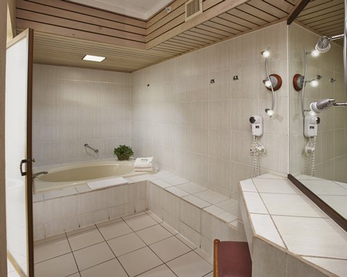 A bathroom with a bathtub and shower stall.