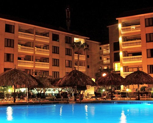 An outdoor swimming pool with chaise lounge chairs alongside the resort units at night.