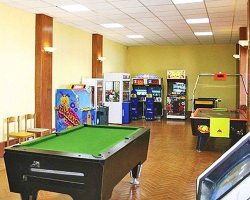 Indoor recreation room with arcade games pool table and air hockey.