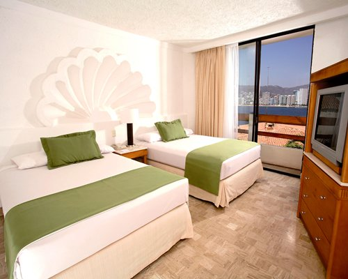 A well furnished bedroom with two beds television and an outside view.