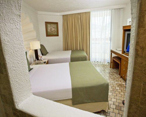 A well furnished bedroom with multiple king beds and a television.