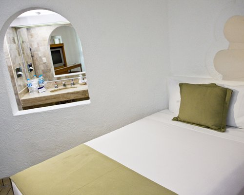 Furnished bedroom with a king bed alongside a bathroom.