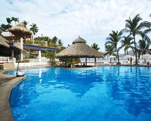 A large outdoor swimming pool with thatched sunshades alongside the resort.