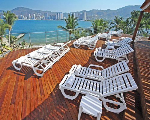 A view of chaise lounge chairs facing the ocean.