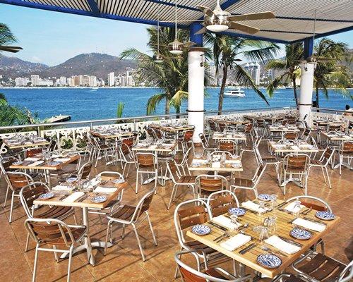 An outdoor restaurant at Playa del Secreto resort alongside the waterfront.