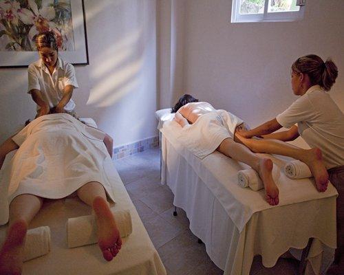 Women enjoying a massage in spa.