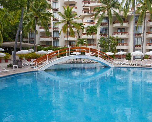 An outdoor swimming pool with chaise lounge chairs and bridge alongside the resort units.
