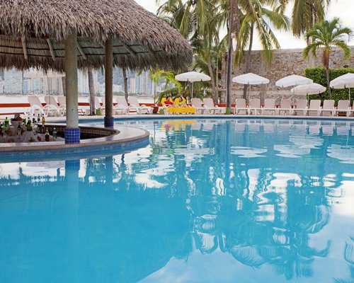 An outdoor swimming pool with a pool side bar and chaise lounge chairs with sunshades.