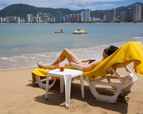 A woman relaxing in a chaise lounge chair facing the ocean.