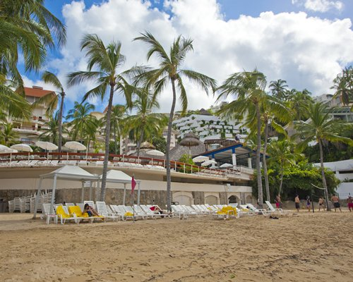 A view of chaise lounge chairs in the beach alongside the multi story units.