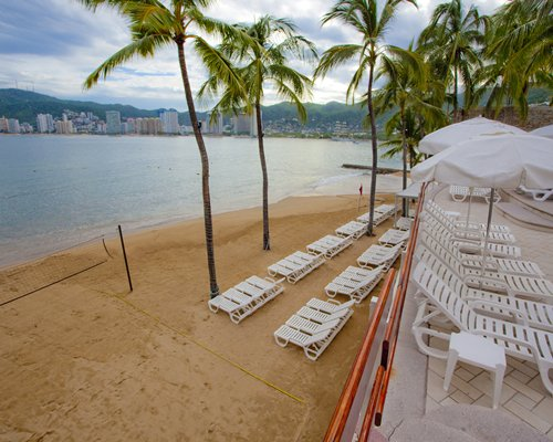 Balcony view of chaise lounge chairs facing the ocean.