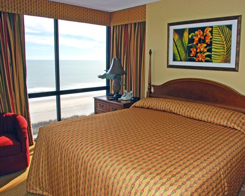 A well furnished bedroom with a queen bed and beach view.