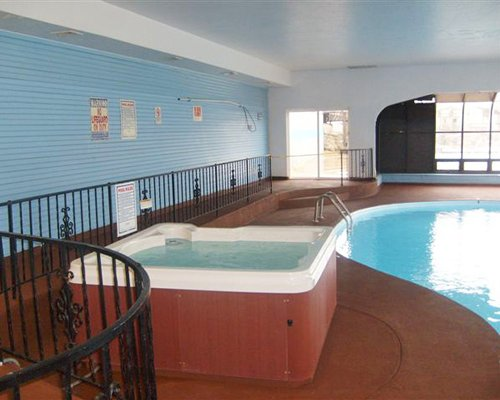 Indoor swimming pool with a hot tub and outside view.