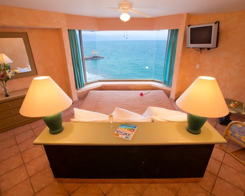 A well furnished bedroom with two lamps television and an ocean view.
