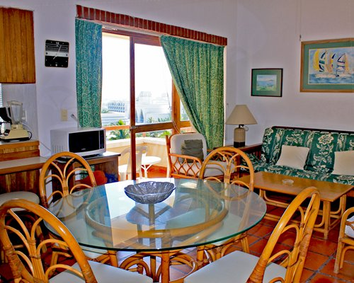 A well furnished living room with dining area open plan kitchen and balcony.
