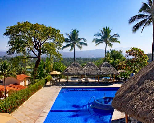 Outdoor swimming pool with poolside bar chaise lounge chairs and thatched sunshades.