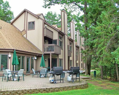 Scenic view of an outdoor dining area with barbecue grills alongside multi story resort unit.