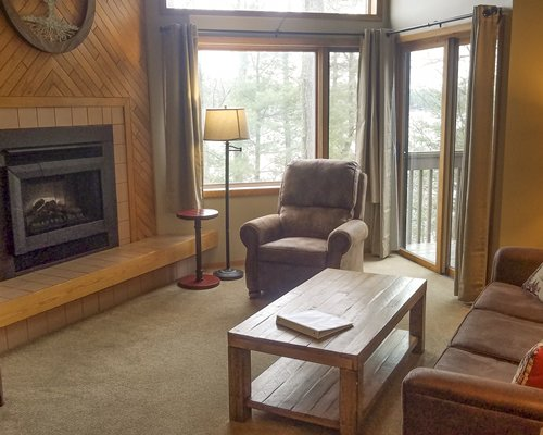 A well furnished living room with a fireplace and an outside view.