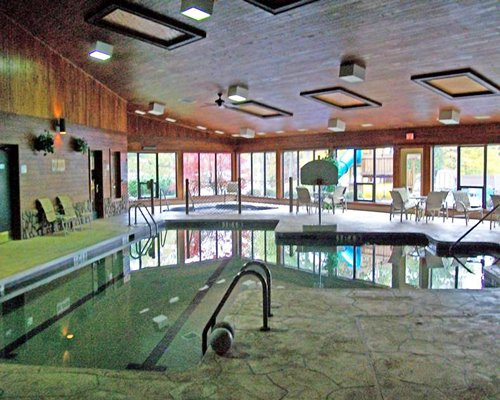 An indoor swimming pool hot tub and patio furniture.