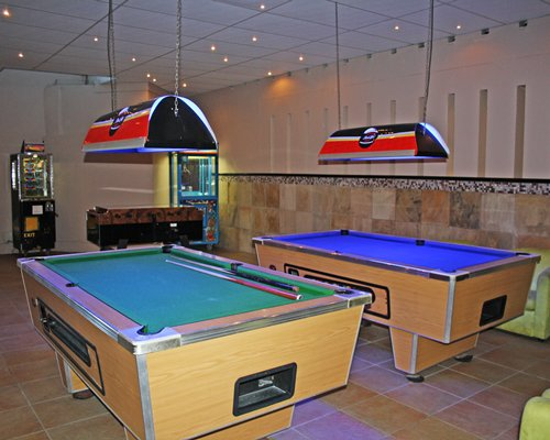 An indoor recreational room with two pool table and arcade games.