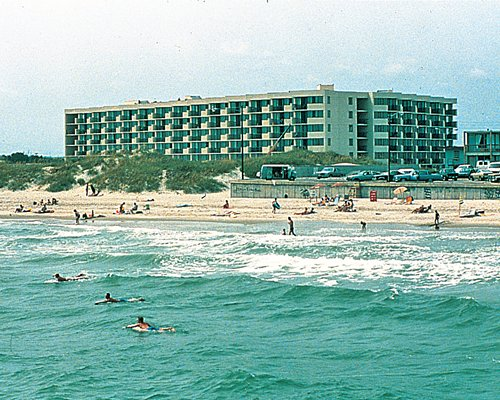Exterior view of Sands Villa Resort alongside the beach with people surfing.