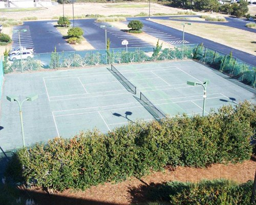View of two outdoor tennis courts alongside the parking lot.