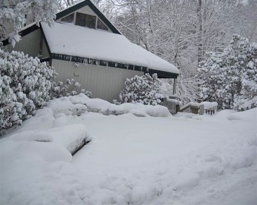 An exterior view of Mossy Creek on Sugar Mountain resort unit covered in snow.