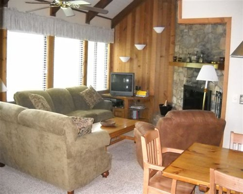 A well furnished open plan living and dining area with a television and a fireplace.
