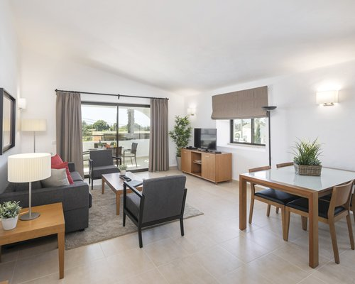 A well furnished open plan living and dining area with a television and a balcony.