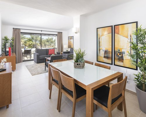 A well furnished living room with dining area television balcony and patio chairs.