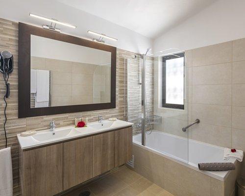 A bathroom with bath tub and two single sink vanity.