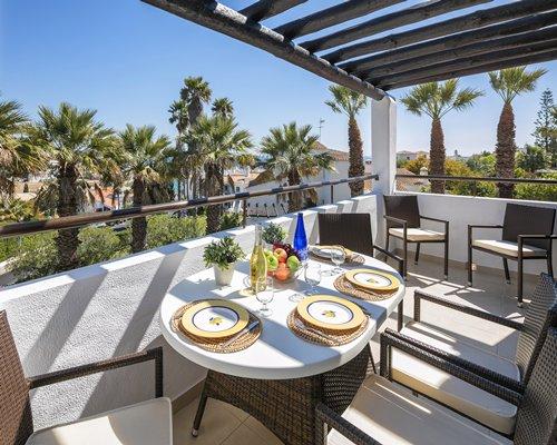 A balcony with dining setup alongside the palm trees.