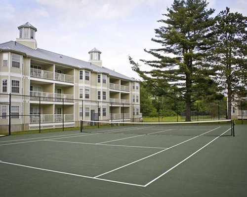 A scenic outdoor tennis court alongside multi story units.