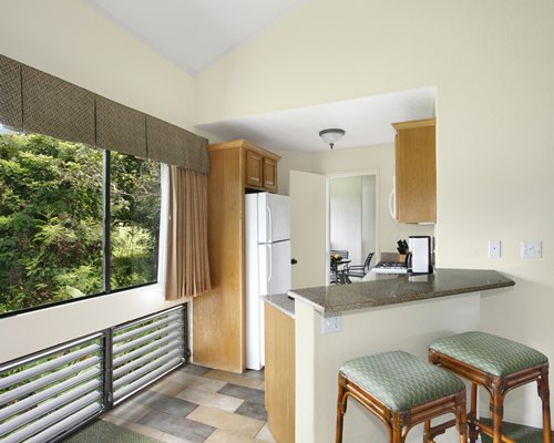 A well equipped kitchen with breakfast bar and an outside view.