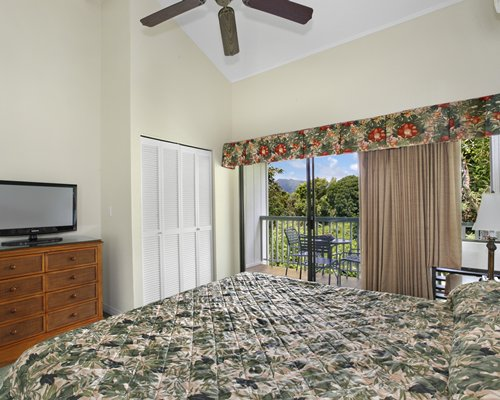 A well furnished bedroom with king bed television and patio.