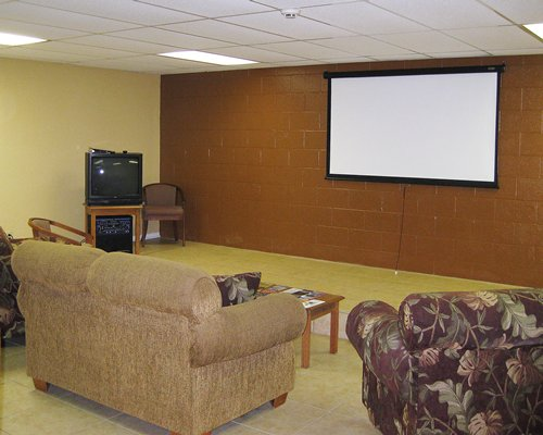 A well furnished lounge area with television and projector.