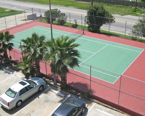 An outdoor tennis court alongside the parking lot.