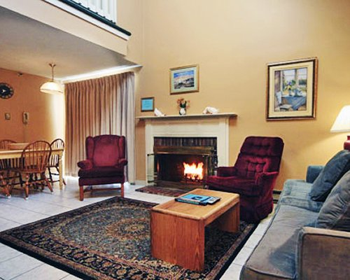 A well furnished living room with fire at the fireplace alongside the dining area.