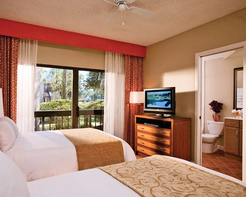A well furnished bedroom with television and an outside view.