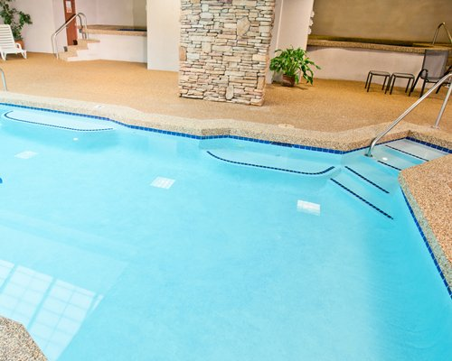 An indoor swimming pool with patio furniture.