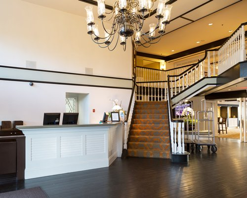 A well furnished reception area with chandelier alongside the staircase.