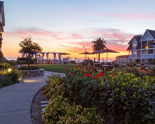 Scenic pathway leading to units at Carlsbad Inn Beach Resort with outdoor dining alongside the beach at dusk.