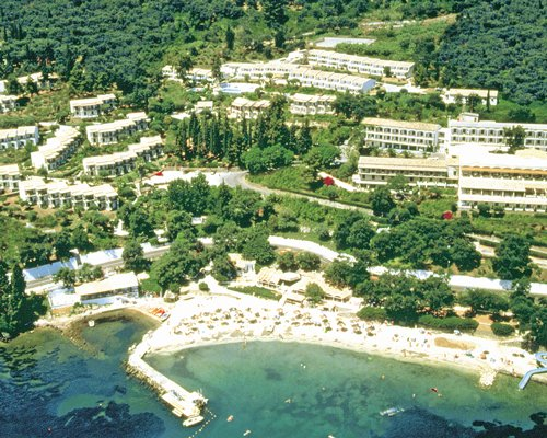 An aerial view of Aeolos Beach Club set in a wooded alongside the sea.
