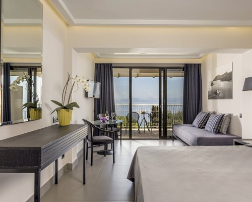 A well furnished bedroom with a dining area and balcony.