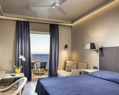 A well furnished bedroom with a balcony and a beach view.